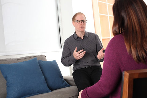 Wade Repta is wearing a black collared shirt is perched on a sofa arm as he speaks to a woman wearing a purple sweater and is seated in a chair facing him