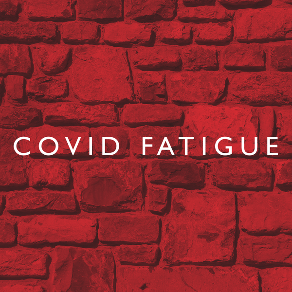 COVID Fatigue is written in white lettering in front of a red brick background
