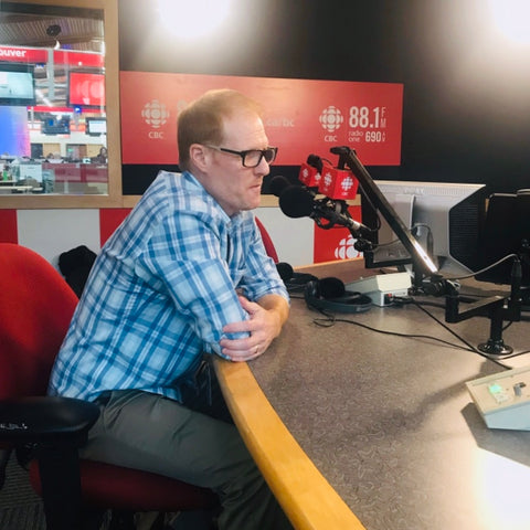 Wade Repta is sitting at a desk, speaking into a microphone during a CBC radio interview