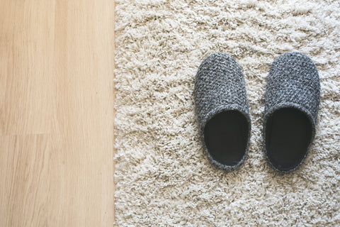 Slipping into the home life, grey slippers on white mat