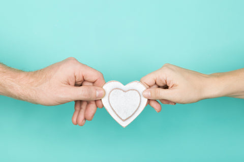 Two hands are holding a cutout paper heart in front of an aqua green background