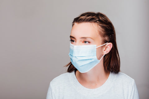 Woman in white shirt is wearing a blue disposable mask in front of a grey background