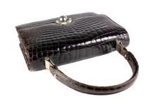Brown crocodile skin handbag with flap and decorative clasp