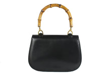 Black leather handbag with bamboo handle and lock