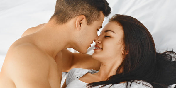 man kissing woman on the bed