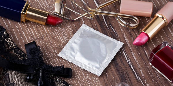 condom surrounded by lipsticks and lingerie