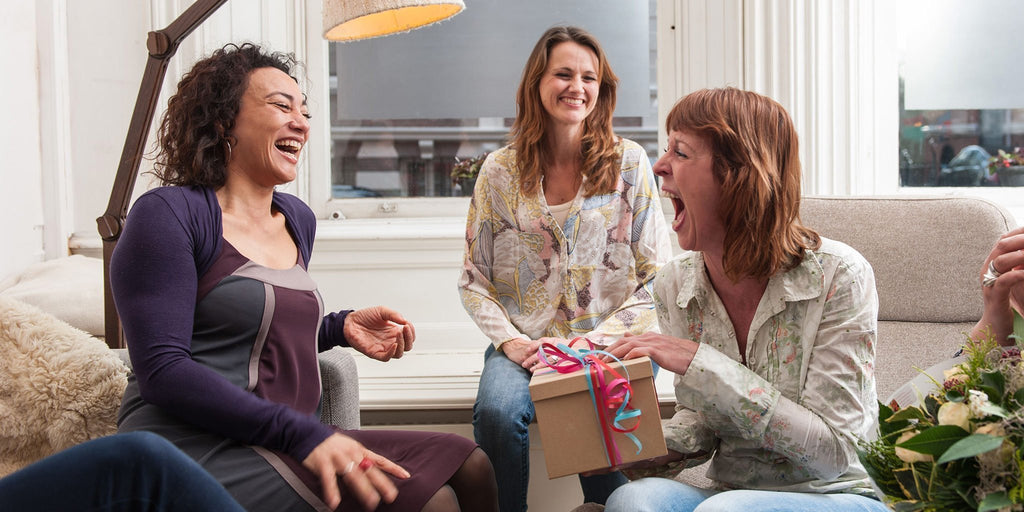 3 women with a gift box laughing