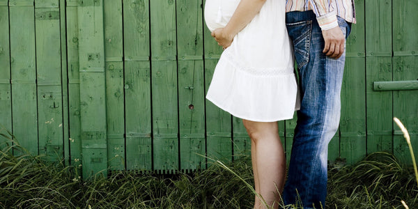 Side-view-of-a-pregnant-woman-stood-back-to-back-with-a-man