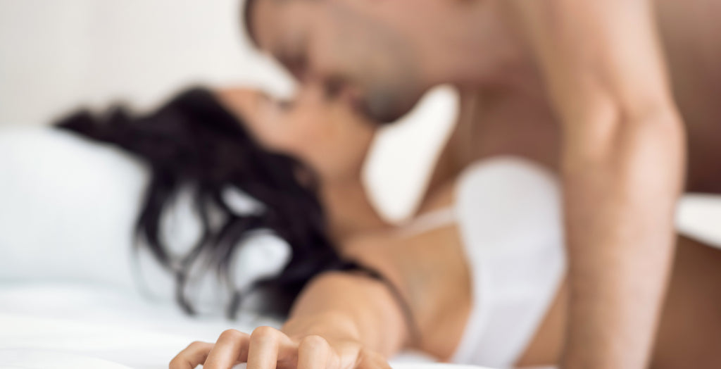 Couple kissing on a white bed