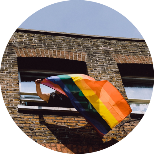 Person waving Pride flag from window