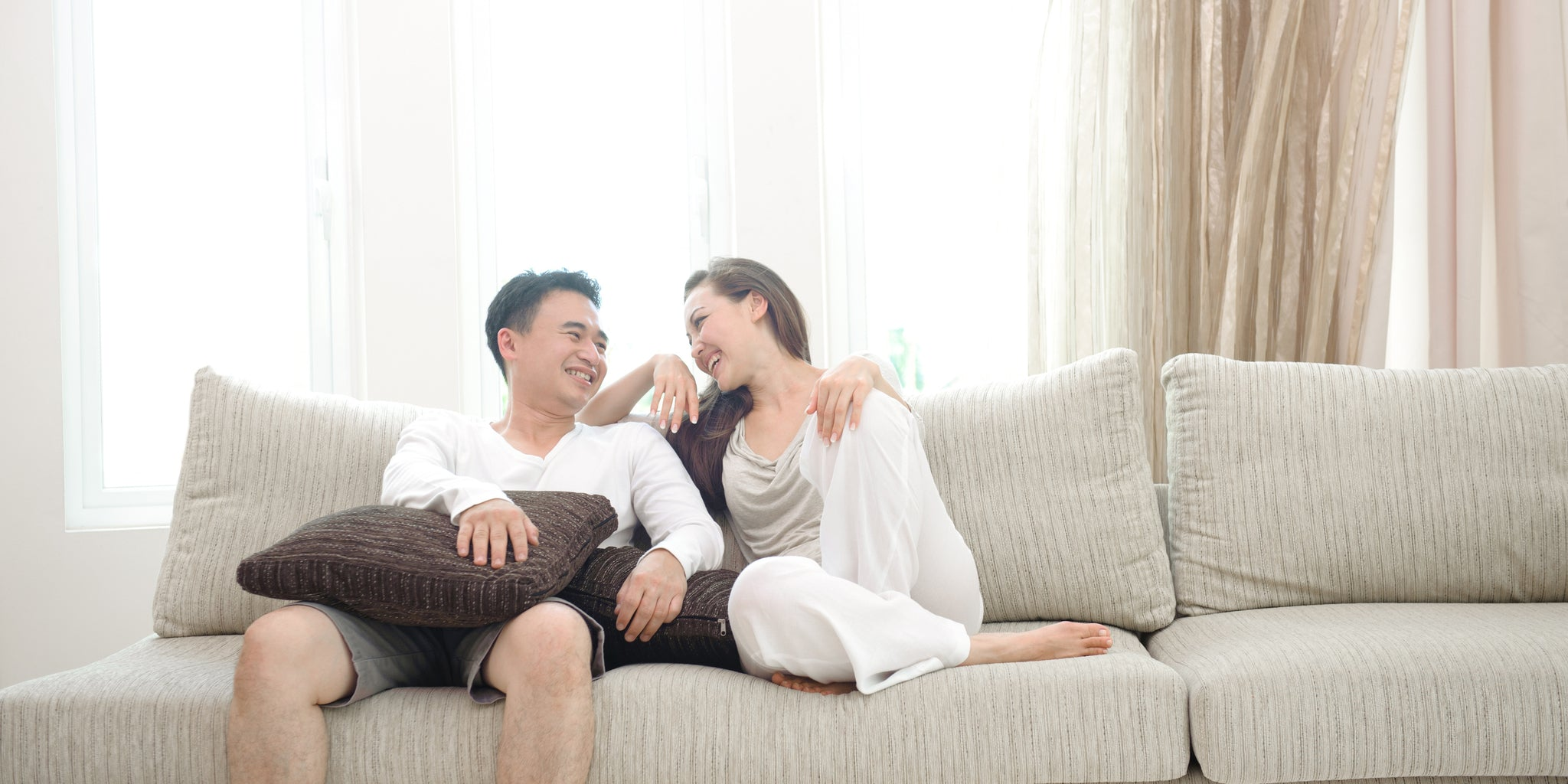 happy-couple-laughing-together-on-the-sofa