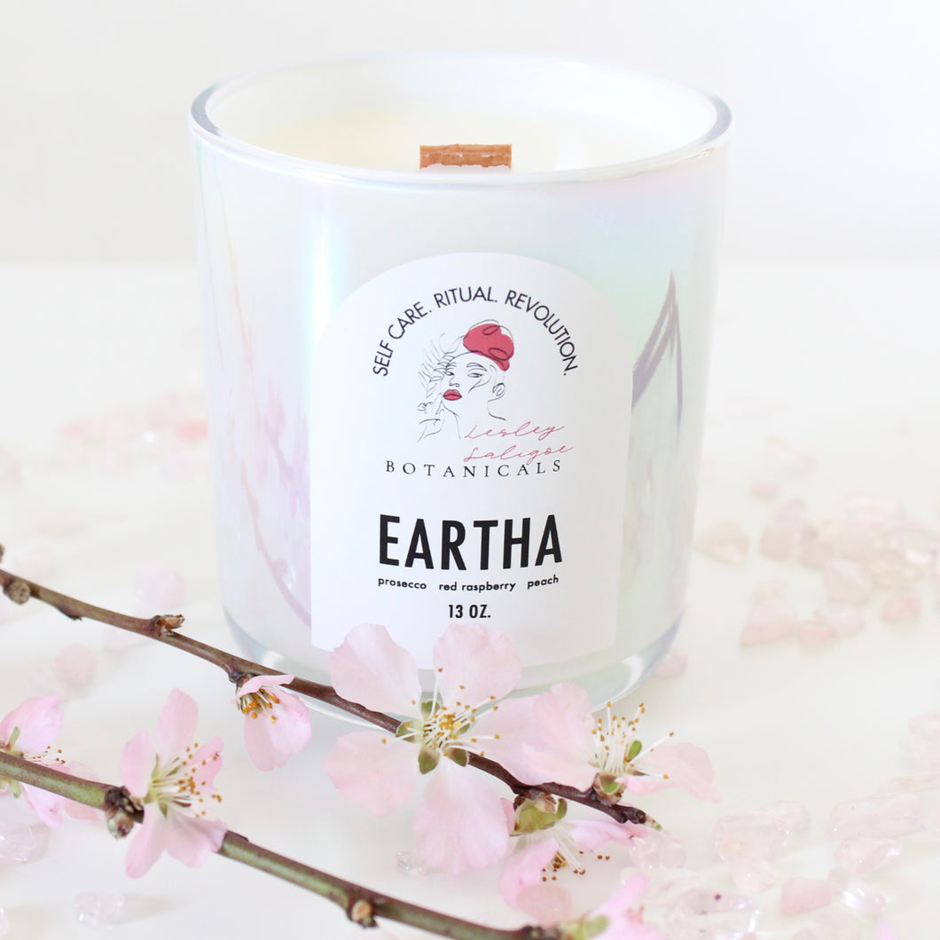 Lesley Saligoe Botanicals Eartha candle surrounded by blossoming branches and rose quartz.