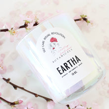 Load image into Gallery viewer, Lesley Saligoe Botanicals Eartha candle surrounded by blossoming branches and rose quartz.