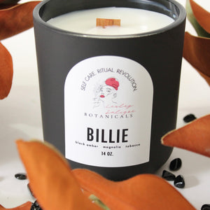 Lesley Saligoe Botanicals Billie candle surrounded by magnolia leaves and black tourmaline crystals.