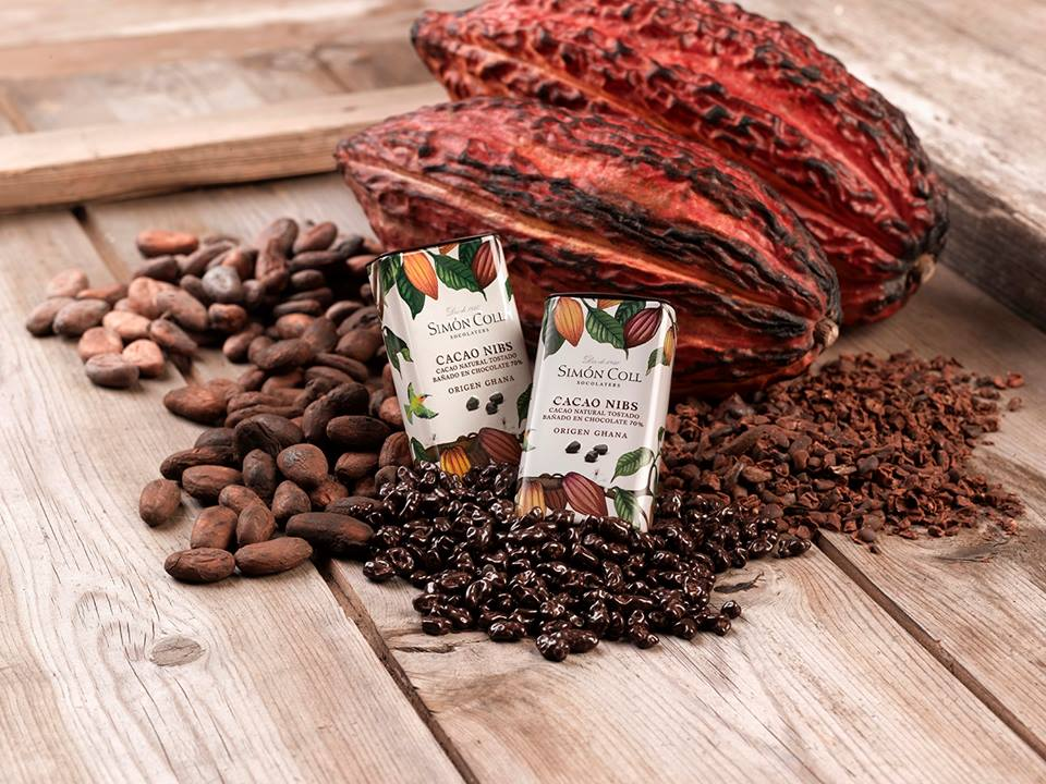 Simon Coll Cocoa Nibs covered in 70% Ghana chocolate 30g Tin with Cocoa beans arrangement
