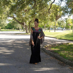 Mexican long black dress, multicolor floral embroidery, on a road