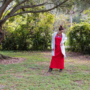 Mexican long red dress, multicolor embroidery, on a forest