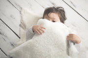 toddler peeking out from under a Nature's Fleece sheepskin rug