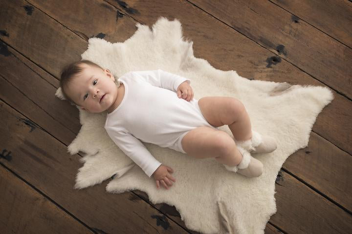baby lying on Nature's Fleece sheepskin rug with wool booties