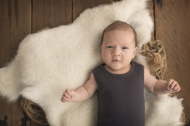 baby lying on Nature's Fleece sheepskin rug looking at camera