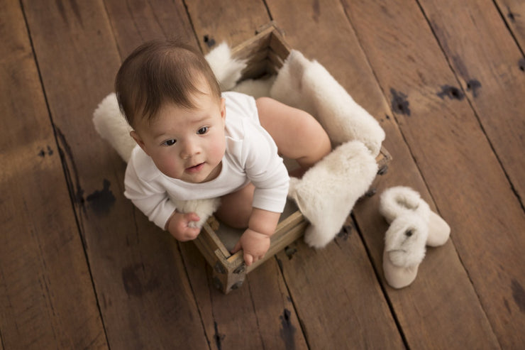 baby sitting on Nature's Fleece sheepskin rug with wool booties