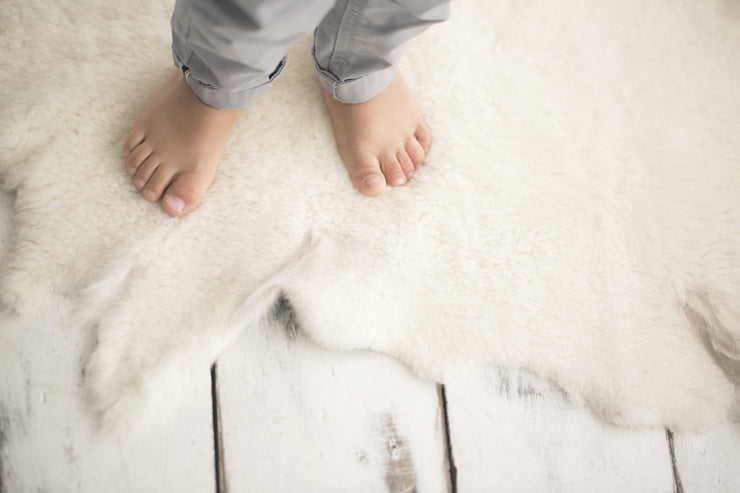 toddlers feet standing on Nature's Fleece sheepskin rug
