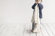 toddler standing holding a Nature's Fleece sheepskin rug