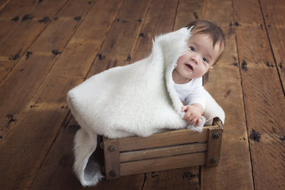 baby peeking out from under a Nature's Fleece sheepskin rug