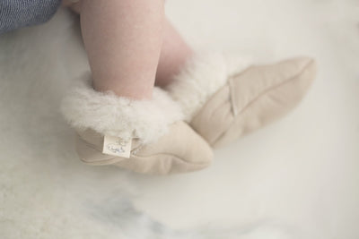pair of Natures Fleece silken wool cream booties on baby's feet