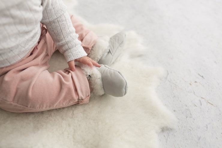 pair of Natures Fleece silken wool grey booties on baby's feet