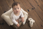 baby sitting on Natures Fleece silken wool rug with booties