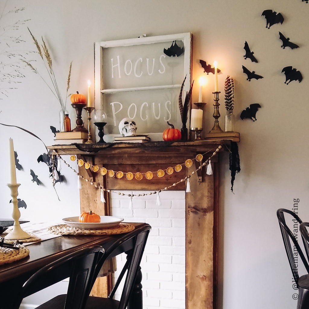 Halloween Mantle with bat silhouettes garland rustic mantle with lighted candles and vintage window