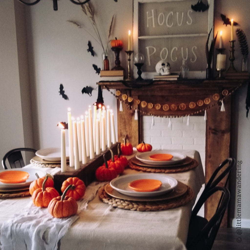 Wooden Candle Holder in front of a wooden mantle with halloween decor and lit candles.