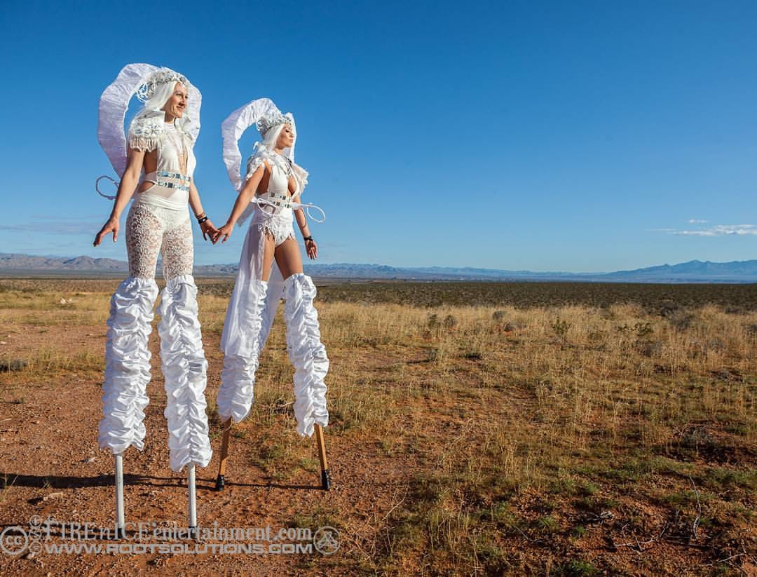 Two Goddess on stilts with white horned headpiece against a spanning desert background