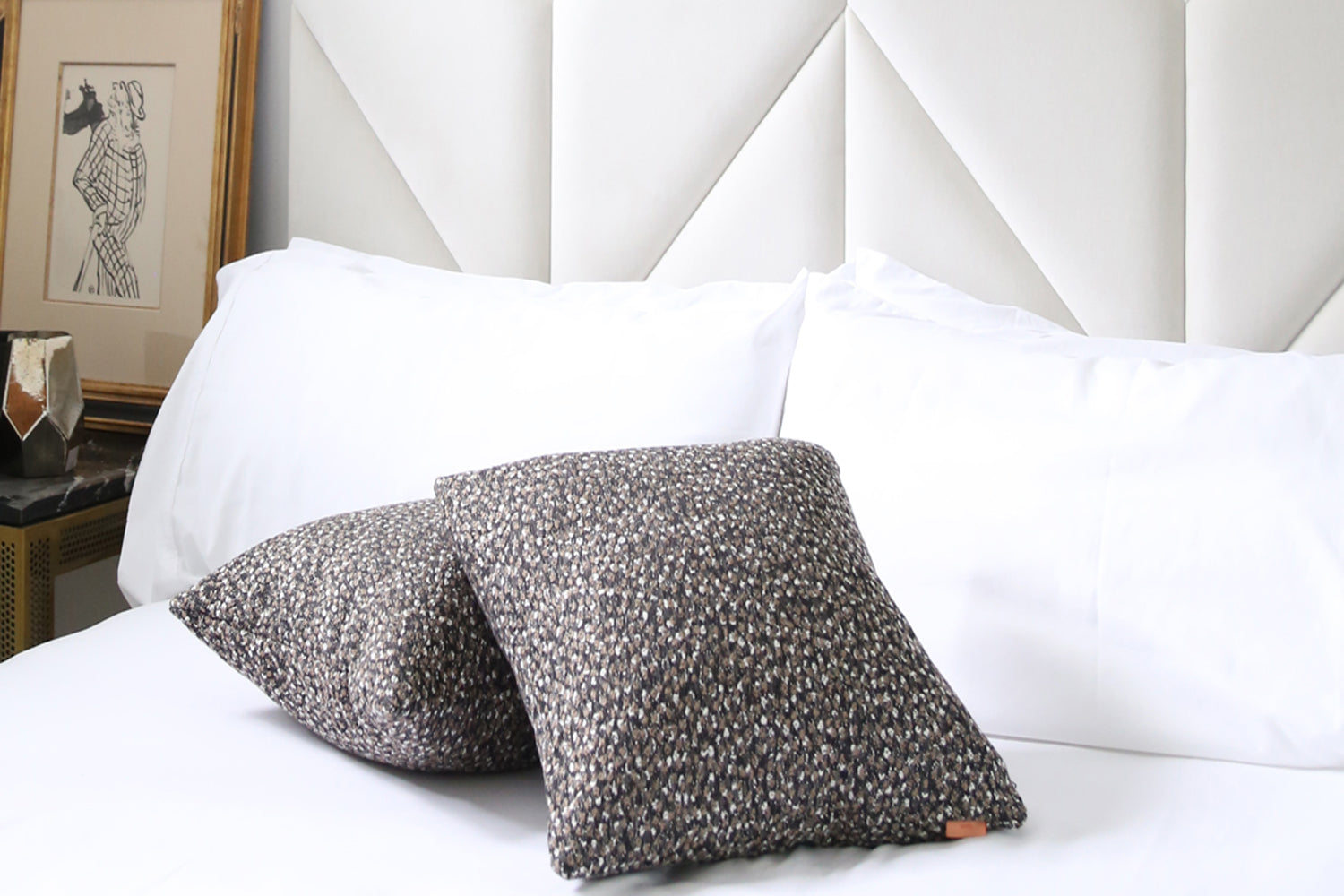designer fabric toss pillows on a bed