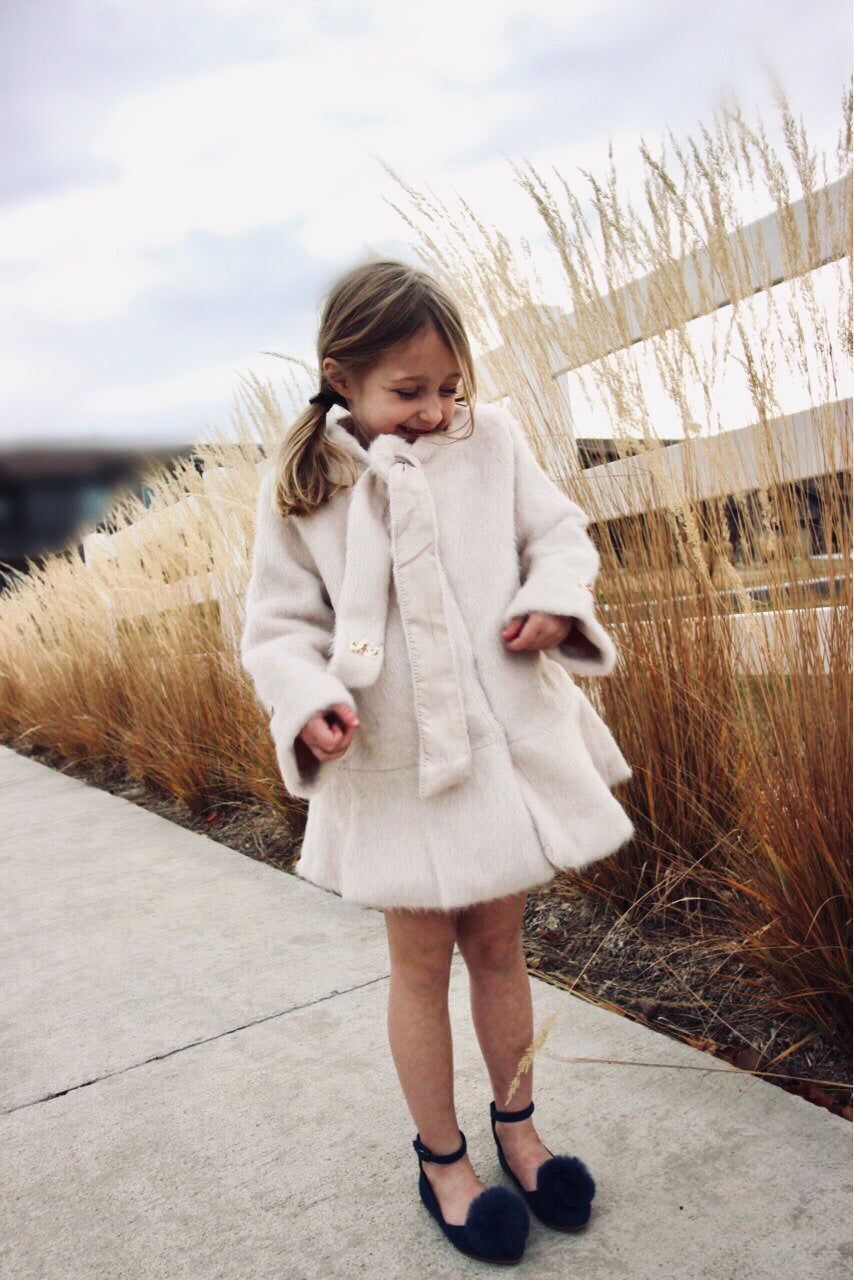 Winter white coat with bow and sequin crown detail