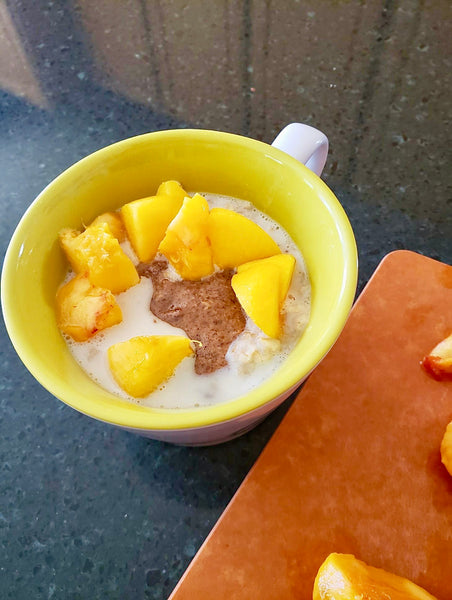 "Peach ""cobbler"" with fresh Colorado peaches, Cinnamon Almond butter and oats cooked in milk."