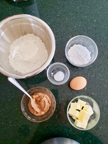 Fresh ingredients for apple tart dough - egg, flour, butter, salt, powdered sugar