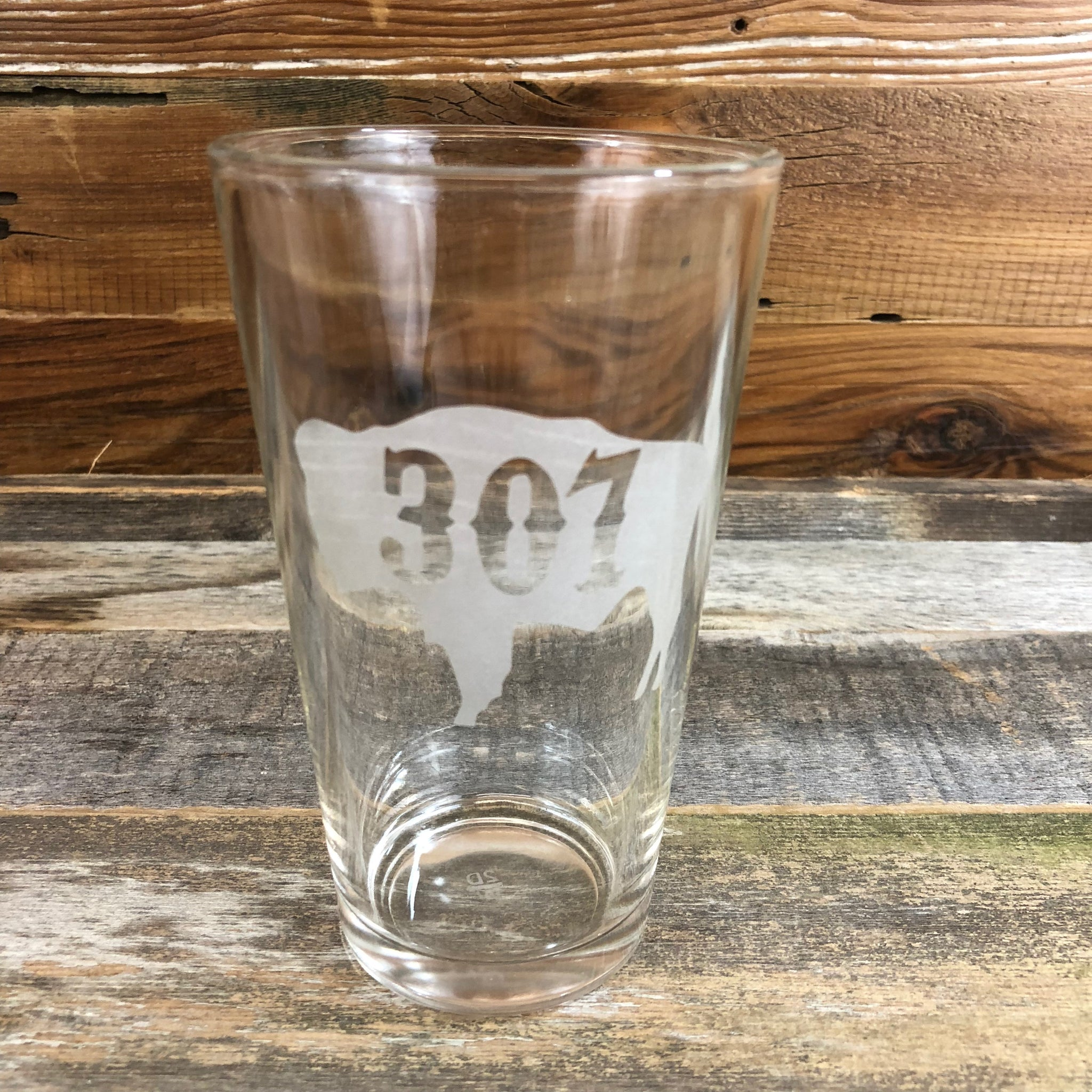 307 Bison Pint Glass Enjoy your favorite beverage in our 16oz capacity pint glass with the '307' designed right into the Wyoming Bison.  Be a part of the herd with a 307 Bison Pint Glass from WyoMade.  Capacity 16 oz    WyoMade is a Wyoming Craft Apparel brand located in the heart of Downtown Casper, Wyoming.