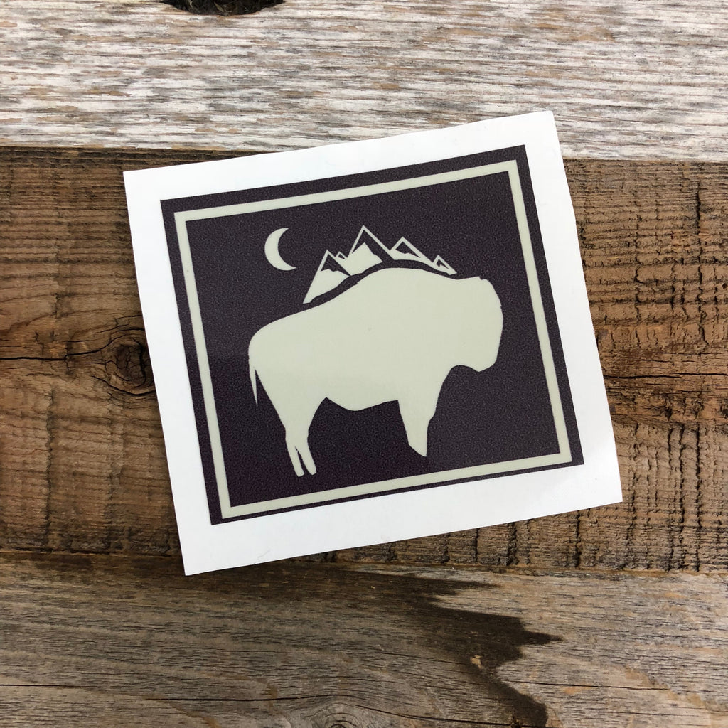 "The New Bison Moon is a modern twist on our long time iconic design from WyoMade!   The Bison represents freedom and is a staple of Wyoming's open spaces. This sticker is sure to appease your desire to roam free.  Be a part of the herd with the Bison Moon design, squared up, from Wyomade.     Size:  2.6"" x 3"""