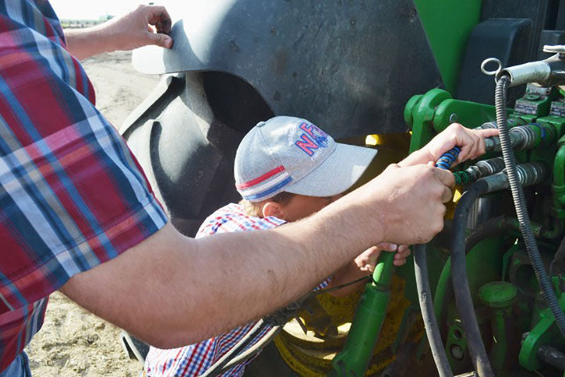 A father and son install outback wrap hydraulic hose markers on their tractor
