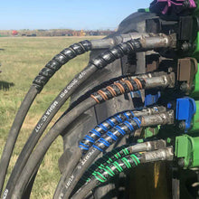 The Outback Wrap 4-pack of hydraulic hose color markers on a tractor in a field.