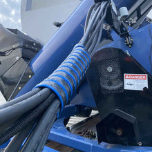 Hydraulic hose tamer in blue keeping many hydraulic hoses together in a group.