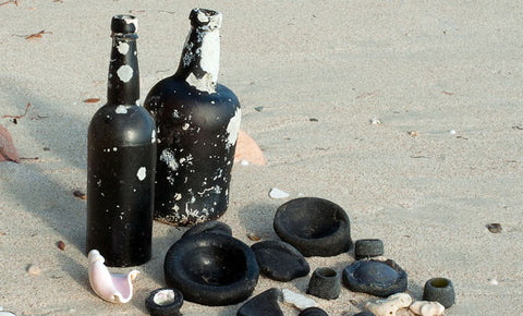 black glass bottles on beach sea glass