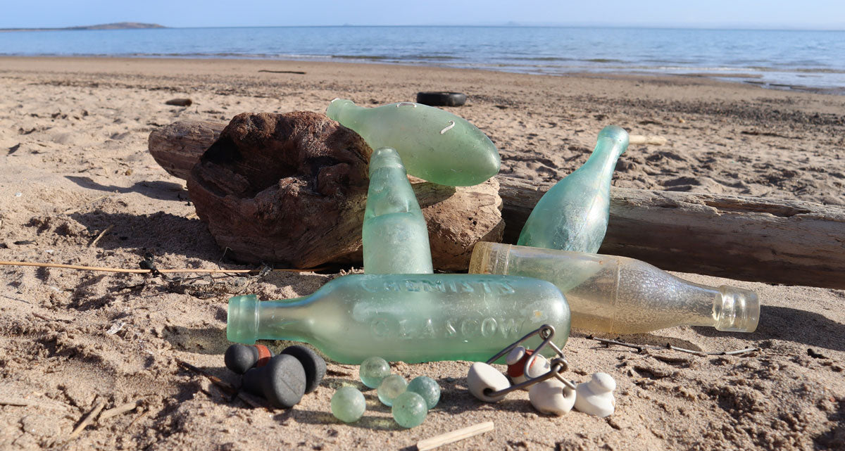 antique carbonated water bottles on beach