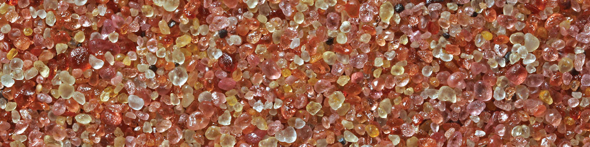 pink and yellow garnet sand under a microscope