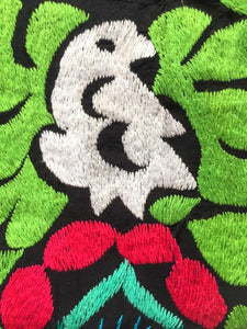 close up to detail of the white parrot hand embroidered  surrounded by bright pink and green flowers