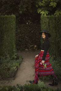 model walking  in a garden wearing a red rebozo as a skirt and a black hat, boots and top