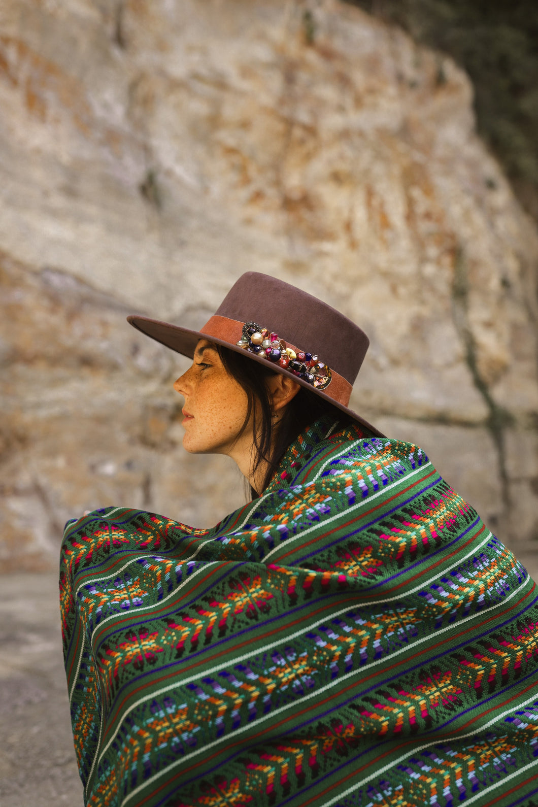 model wearing a green handmade wool rebozo and a brown hat boho vibes