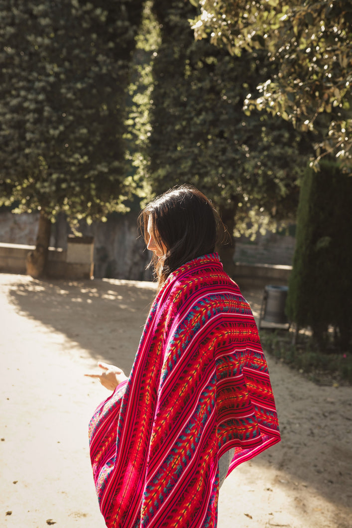 model wearing a bright pink rebozo covering her back